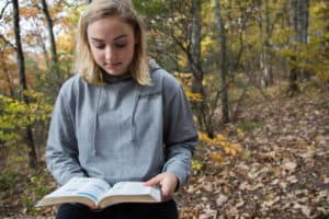 Young woman reading bible in the woods